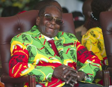Zimbabwean President Robert Mugabe sits in a chair, sunglasses and a smile, wearing a colorful yellow, red, and green jacket