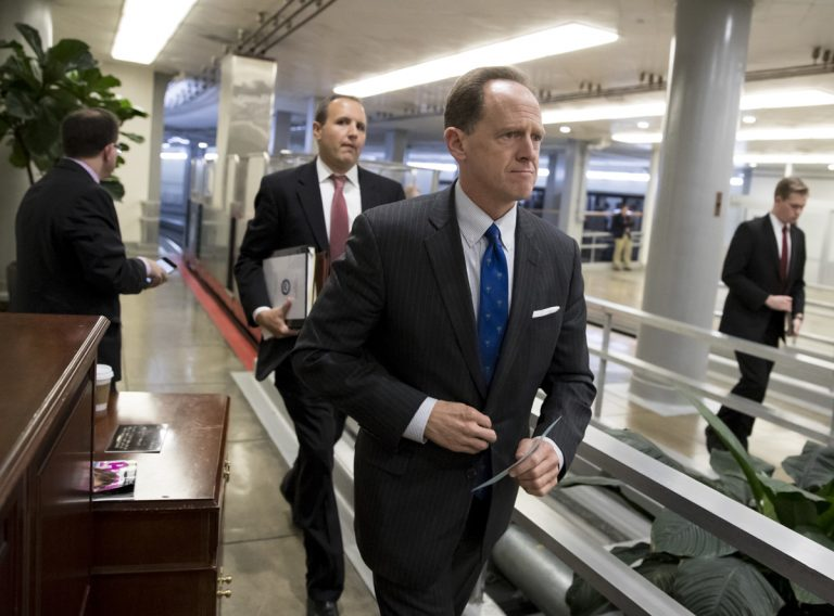 Toomey walks through a hallway in the Capitol