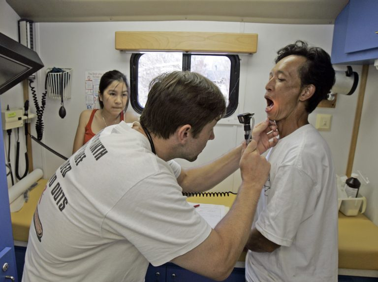 A doctor uses a scope to look into the mouth of a patient; another woman looks on from the rear