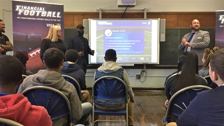 Eagles player Malcolm Jenkins (center left) speaks about financial literacy to students at Bodine High School in Philadelphia (Avi Wolfman-Arent/WHYY)