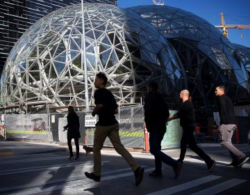 People in shaddow walk past a geometric building (Amazon's Seattle HQ)