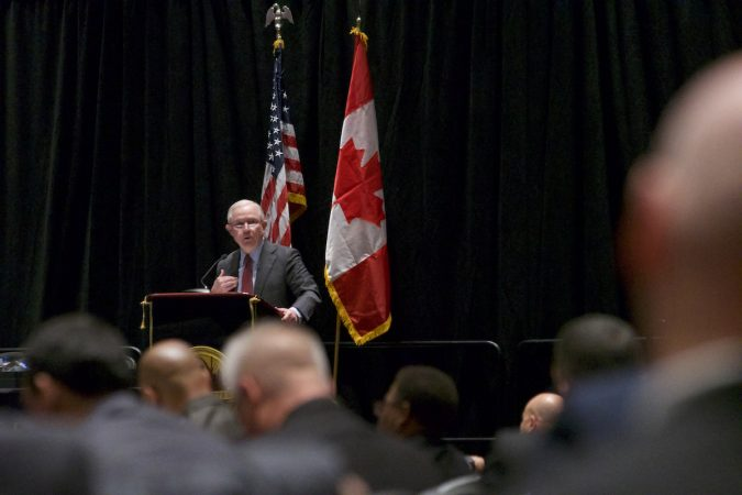 Sessions on stage, the American and Canadian flags stand behind him