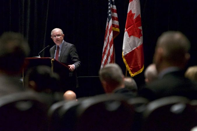 Sessions on stage, American and Canadian flag in the background