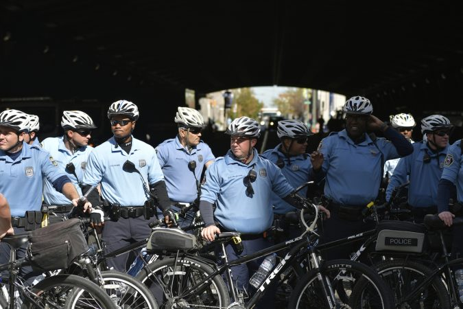 Bycicle officers stand blocking a street