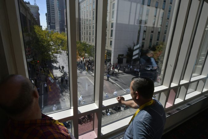 People look down through a window onto the protesters and officers below