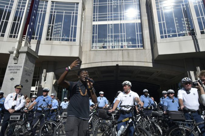 A man speaks in front of a line of officers outside of the convention center