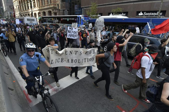Protesters march through the city streets, some masked, some carry a banner