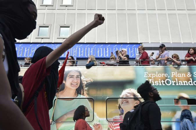 A person holds up a fist in protest as tourists pass by on a double-decker bus