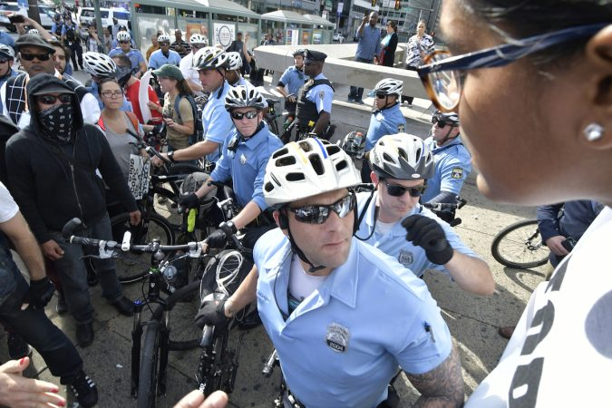 An officer looks to the distance, behind him a group of protesters