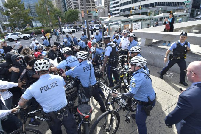 Officers push against a group of protesters