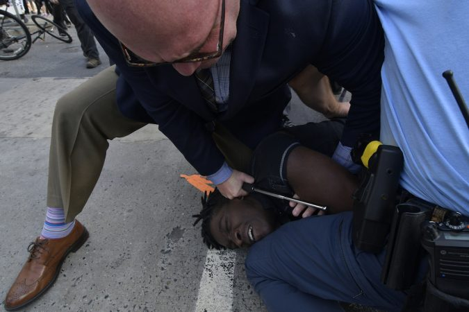 A protester is held on the ground, face down by an officer
