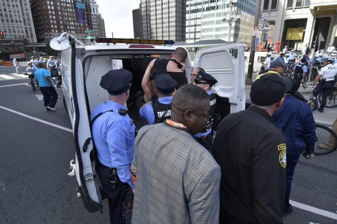Officers load protesers into a police wagon