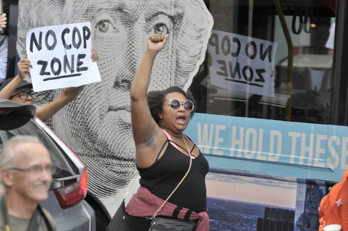 A woman holds her fist in the air, Washington's face, a window decal in the background