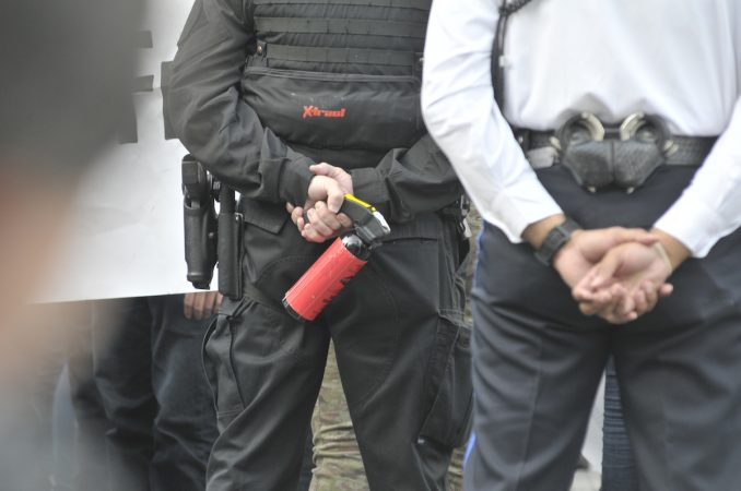 Officers from behind, stand with their arms behind their backs, one holds a can of pepperspray or teargas