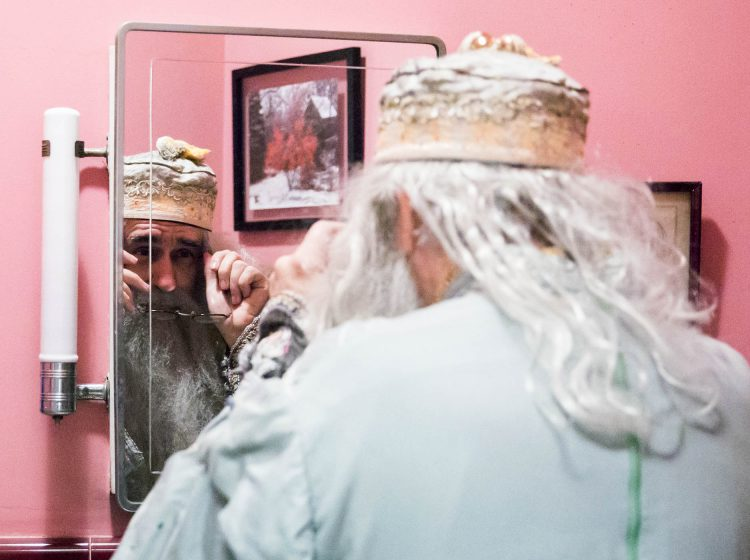 Walt Maguire adjusts his glasses in his bathroom mirror on October 20, 2017. Maguire, 60, played the part of Dumbledore at Chestnut Hill's Harry Potter Festival for six years. Now, he is co-hosting the Witches and Wizards festival costume contest. (Rachel Wisniewski for WHYY)