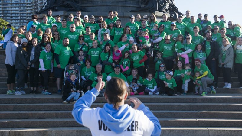 Members of a team, all in green, post on the steps of the Art Museum for a photo before the walk