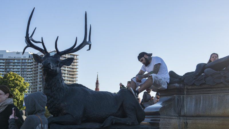 A man sits atop a statue of a stag near the Art Museum