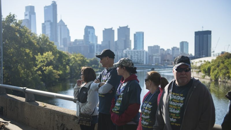 People in matching t-shirts stand against a railing with the city's skyline in the background