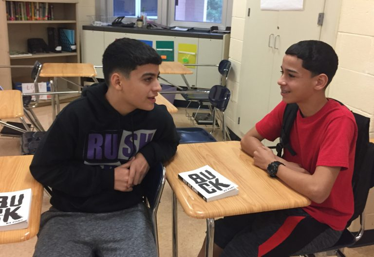 Two schoolboys seated at desks, one turned to the other talking, a book between them,