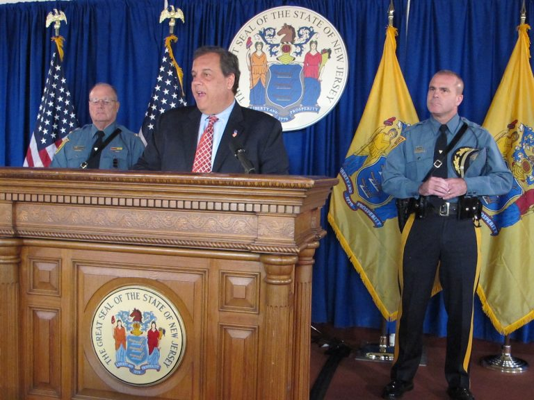Governer Christie stands at a podium flanked by two officers, American flag, and New Jersey flag, and seal
