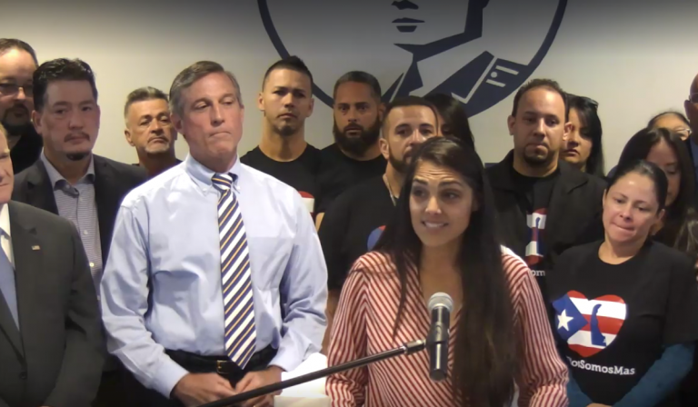 Delaware Hispanic liaison India Colon stands in front of Gov. John Carney as she talks about the devastation she saw in Puerto Rico after Hurricane Maria. (screenshot via Delaware.gov/Livestream)