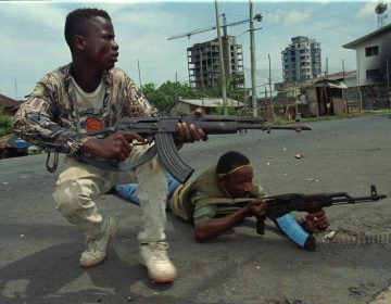 Fighters from the United Liberation Movement of Liberia (ULIMO) shoot their way through downtown Monrovia, LIberia Tuesday, April 16, 1996.