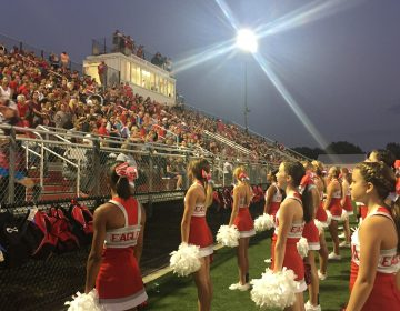 Smyrna High fans and cheerleaders gush with enthusiasm as the two-time defending state champion Eagles get ready to play their first home  game in 2017.  (Cris Barrish/WHYY)