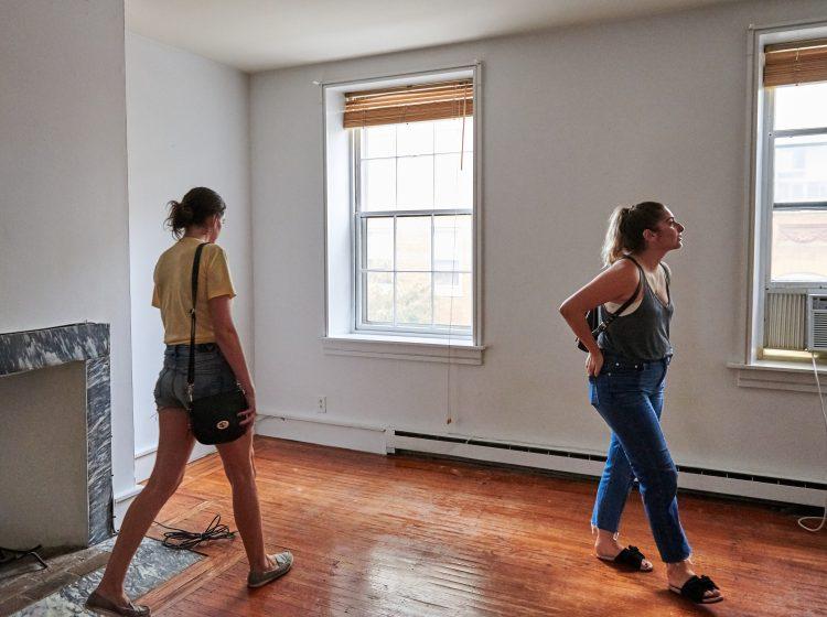 Prospective renters Lisa Schaufler (left) and Alyssa Koenigsberg tour a brownstone in Society Hill. (Natalie Piserchio for WHYY)