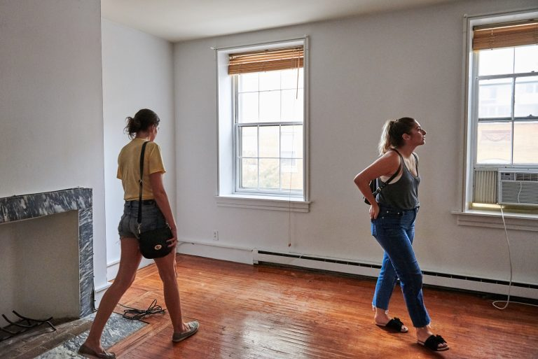 Prospective renters Lisa Schaufler (left) and Alyssa Koenigsberg tour a brownstone in Society Hill. (Natalie Piserchio for WHYY)