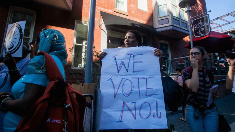 A closeup of the woman with the 'we vote no sign'