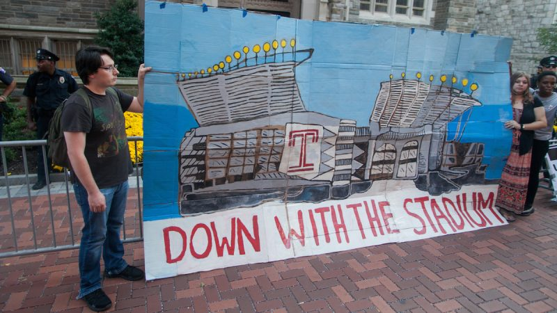 People hold a large, painted cardboard sign depicting the stadium in question, saying 'down with the stadium'