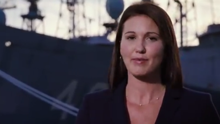 A woman speaks with a warship in the background
