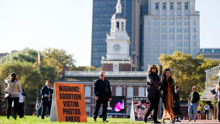 Visitors of Independence Mall in Philadelphia walk past signs both depicting and warning of graphic images. Created Equal, the anti-abortion group that is Columbus, Ohio-based, sponsored the protest. (AP Photo/Matt Rourke)
