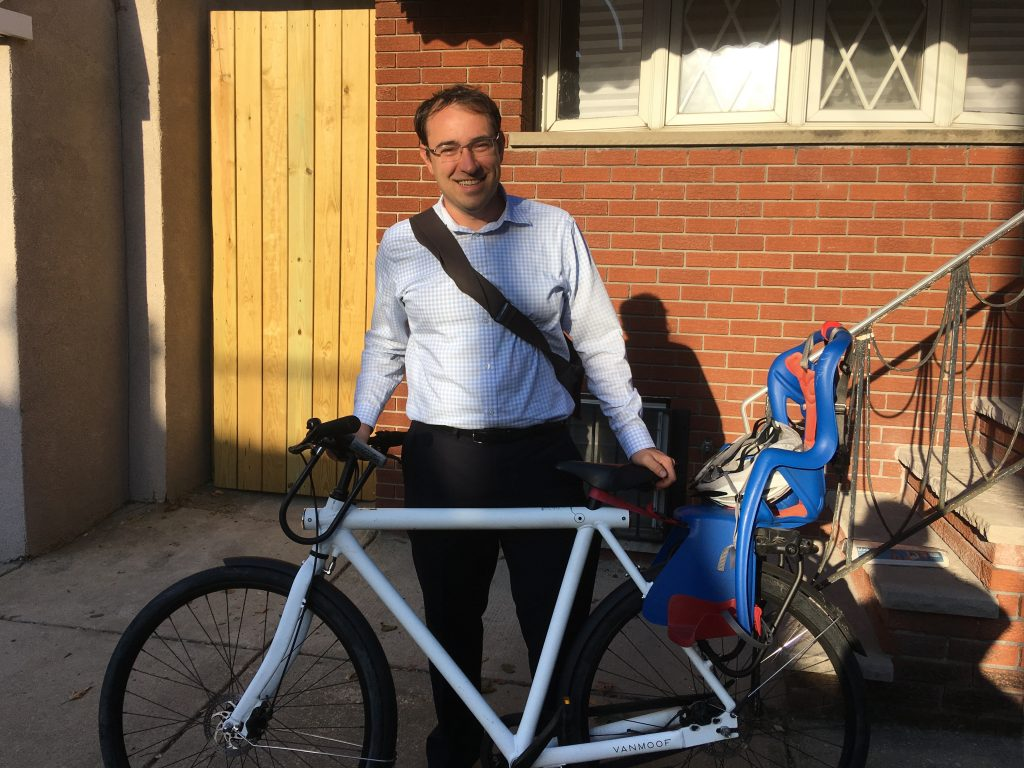 Andrew Stober stands with his VanMoof bike in front of his South Philly rowhome