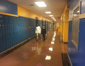 Two students walk towards the camera in an otherwise empty school hallway, blue lockers, yellow walls