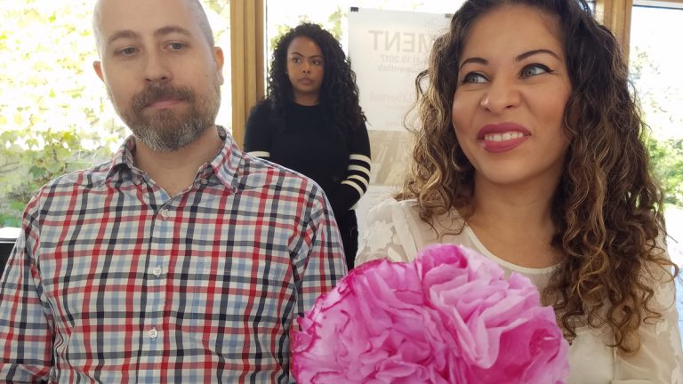 A man in flannel and a woman holding a pink bouquet of paper flowers