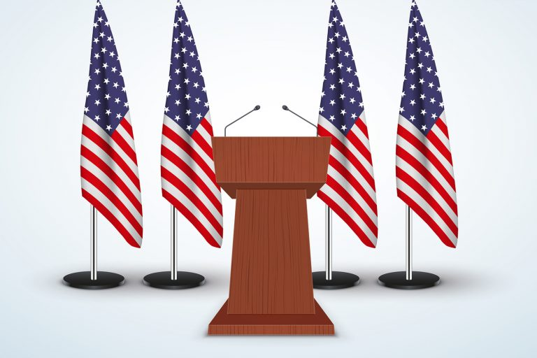 Wooden Podium Speaker Tribune with United States flags on background.