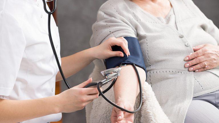 Nurse taking elderly woman's blood pressure in nursing home