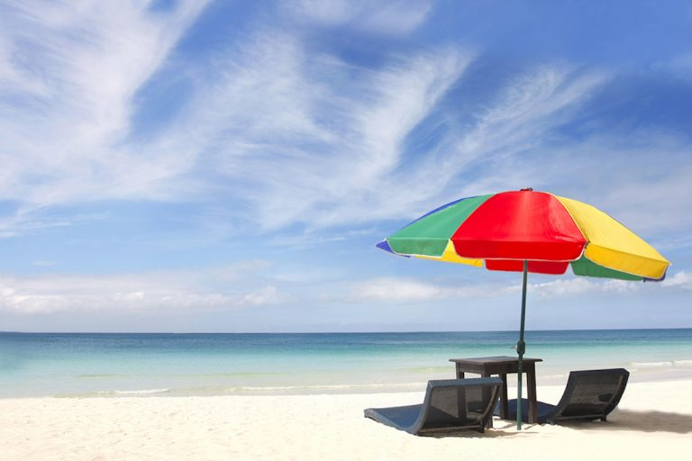 umbrella and chairs on white sand beach (volare2004/BigStock)