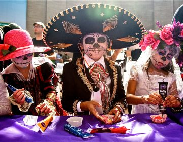Children in costume with skull face paint decorate sugar skulls.