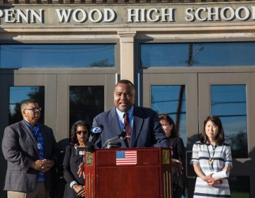 A man at a podium outside the Penn Wood High School