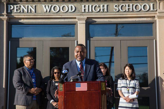 A man at a podium outside the Penn Wood High School