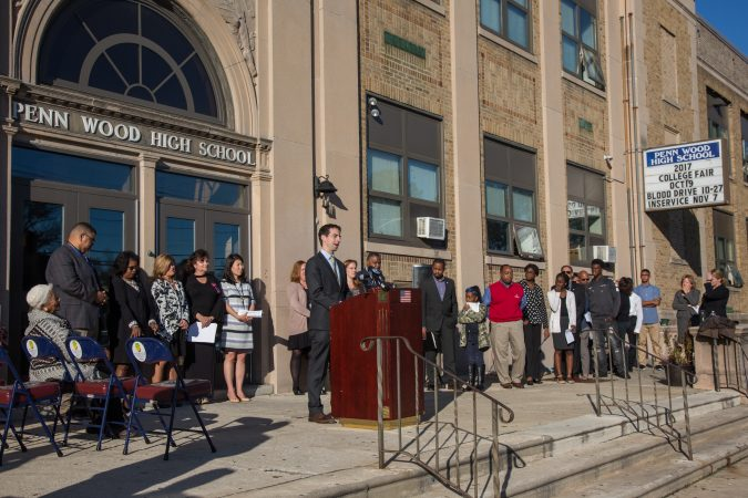 Wide shot of people standing in front of a school, one at a podium