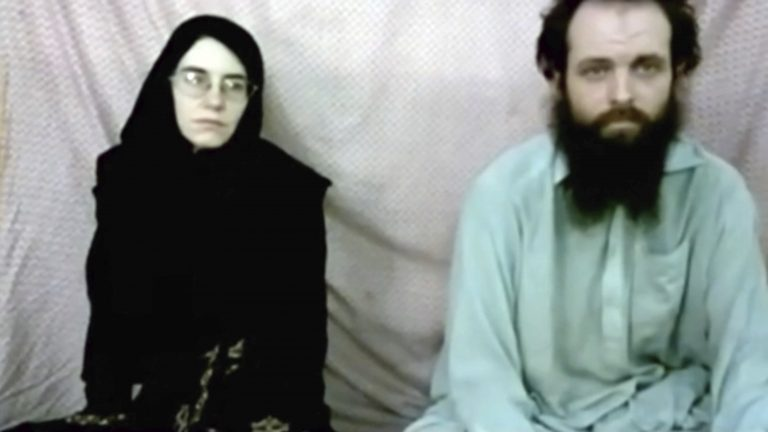 A woman in a burka dn a bearded man; American and Canadian, who've been in captivity