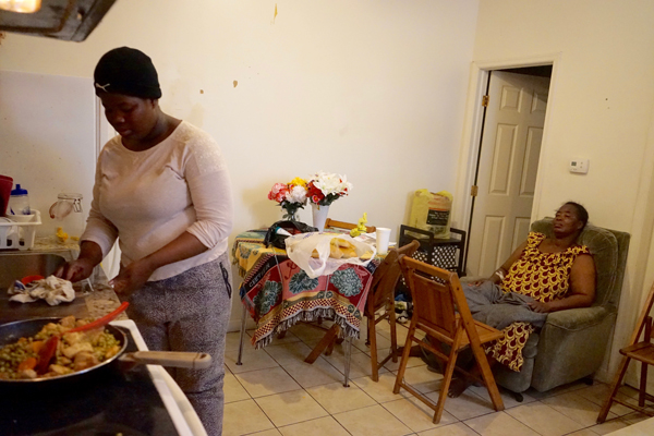 Tatiana Angama, stands at the stove cooking, her mother in the chair off to the right