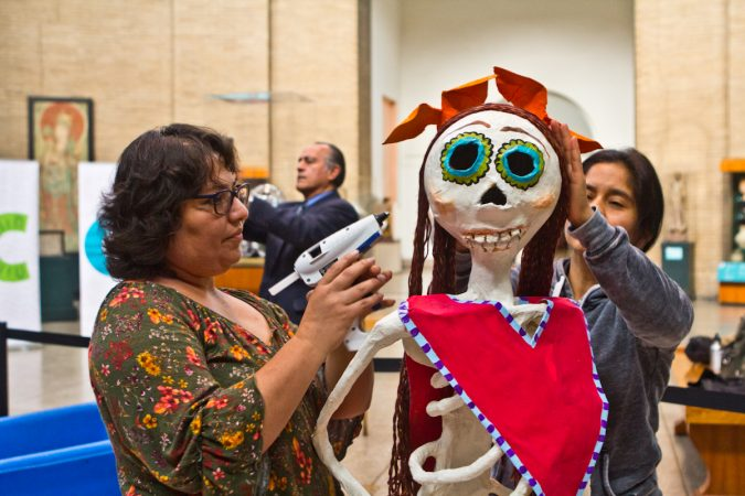 Artists Anna Palma (left) and Ivonne Pinto (right) work on the hair of a character for the Day of the Dead altar at the Penn Museum. (Kimberly Paynter/WHYY)