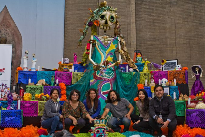Artist Cesar Viveros (center right), coordinated the effort of his pupils and employees of the Mexican Consulate to create the altar. (Kimberly Paynter/WHYY)