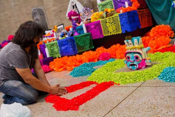 Artist Cesar Viveros arranges paper petals on the floor of the Day of the Dead altar. (Kimberly Paynter/WHYY)