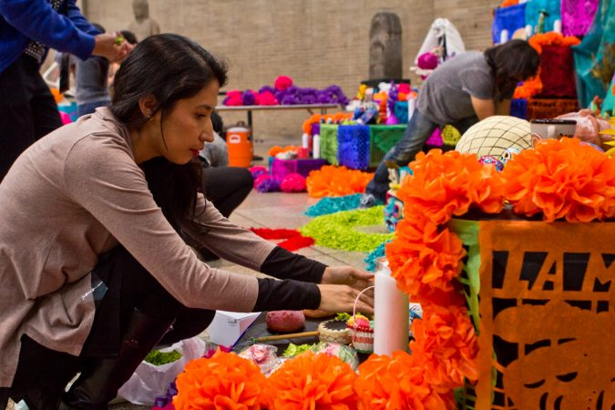 Virginia Rivera, with ether Mexican Cultural Center, arranges sweets on the altar. (Kimberly Paynter/WHYY)