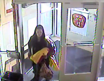 A white female, 25-35 years of age, 5'5″ tall, with a large build, long brown hair, wearing a gray hooded sweatshirt, black leggings and carrying a yellow blanket.